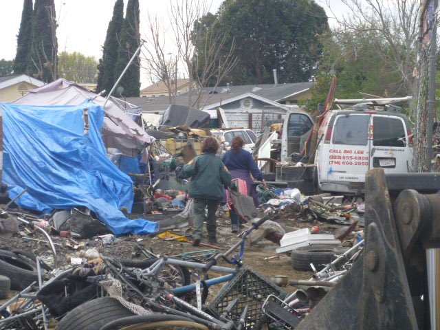 Watts lot next to 1650 E 109th covered in junk